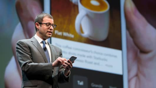 Starbucks' Adam Brotman demonstrates mobile order and pay on the the company's app during the Starbucks annual shareholders meeting.