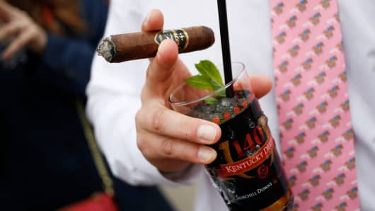 A racegoer holds a cigar and Mint Julep cocktail in the infield at Churchill Downs on the eve of the Kentucky Derby in Louisville, Kentucky.