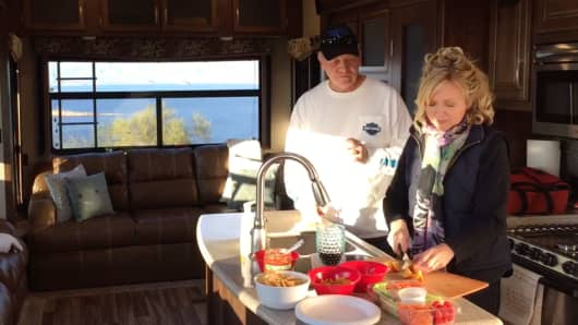 Mark and Holly Batchelder prepare a meal in their RV.