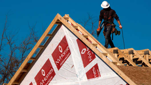 A construction worker installs a rooftop on to a new home being built in Fairfax, Virginia.