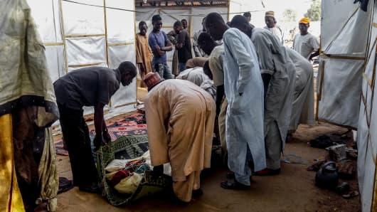 Residents of the Muna camp, near Maiduguri, tend to a blast victim on March 22, 2017.