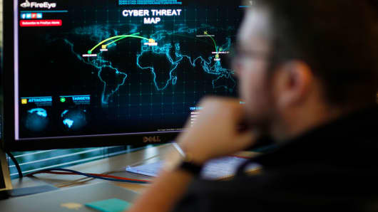 A FireEye information analyst works in front of a screen showing a near real-time map tracking cyber threats at the FireEye office in Milpitas, California.