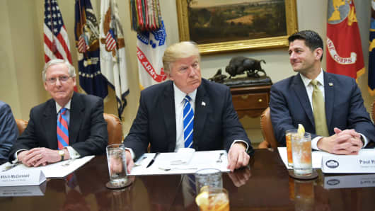 President Donald Trump is seated for a a lunch with Senate Majority Leader Mitch McConnell (L) and House Speaker Paul Ryan.