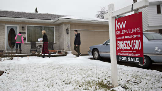 Prospective buyers and a real estate agent, center, enter a home for sale in Warren, Michigan.