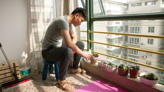 Sun Huifeng, a marketer for an information technology company who rents out one of the rooms in his apartment, waters his window plants, in Beijing, March 11, 2017.