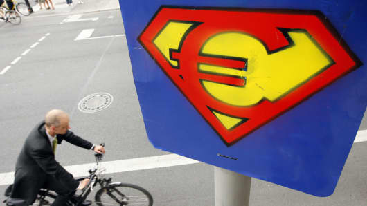 A cyclist passes graffiti of the euro sign shaped into the Superman logo near the Brandenburg Gate in Berlin, Germany.