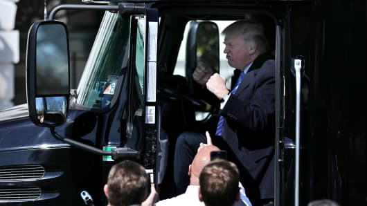 President Donald Trump gets into the drivers seat of a semi-truck as he welcomes truckers and CEOs to the White House in Washington, DC, March 23, 2017, to discuss healthcare.