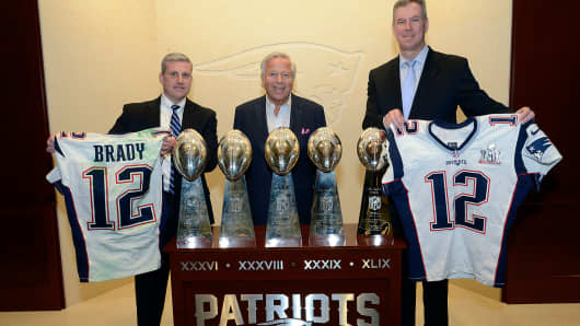 Harold Shaw, left, special agent in charge of the FBI's Boston Division, and Massachusetts State Police Col. Richard McKeon, right, show Tom Brady's recovered jerseys Thursday along with Patriots Chief Executive Robert Kraft, middle.