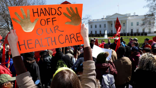 Protesters demonstrate outside the White House in Washington, DC, on March 23, 2017, against President Donald Trump and his plans to end Obamacare. After several failures to repeal the ACA, last week Trump stopped federal payments that have been key to subsidizing ACA coverage for low-income Americans. He also cut the budget to market the ACA during open enrollment season.