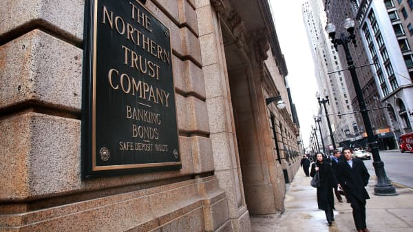 Pedestrians walk by the Northern Trust banking company's headquarters in Chicago, Illinois.