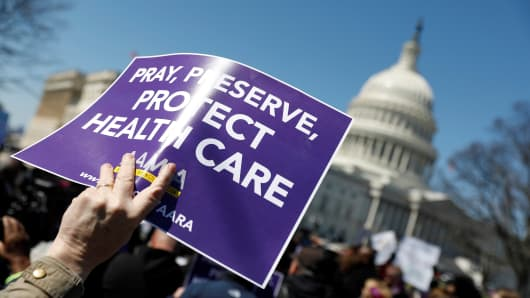 Demonstrators hold signs during a protest against the repeal of the Affordable Care Act outside the Capitol Building in Washington, U.S., March 22, 2017.