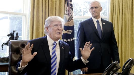 President Donald Trump speaks to members of the media as Vice President Mike Pence looks on, in the Oval Office in Washington, D.C., on March 27, 2017.