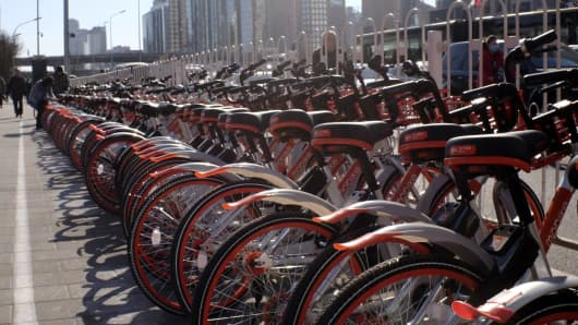Mobike bicycles are seen in line at a docking area along a pedestrian sidewalk at the Central Business District (CBD) in Beijing, March 27, 2017.