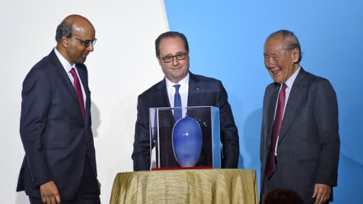 French President Francois Hollande (C) with Singapore Deputy Prime Minister Tharman Shanmugam (L) and Wang Gungwu (R), chairman of the ISEAS Board of Trustees in Singapore on March 27, 2017