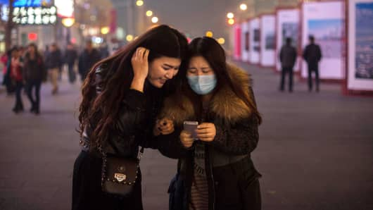 Chinese women look at their mobile phone as they walk in a shopping area in Beijing.