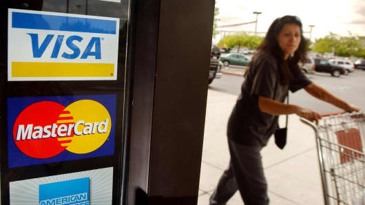 A shopper passes a shop door advertising acceptance of purchases with Master Card and Visa in Bakersfield, California.