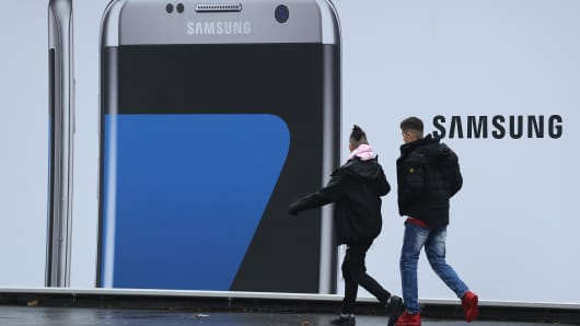 People walk past an advertisement for the Samsung Galaxy S7 Edge smartphone in Berlin, Germany.