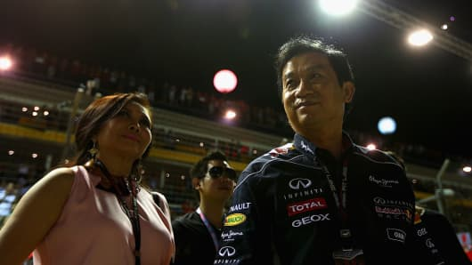 Chalerm Yoovidhya (R) , the father of Vorayuth Yoovidhya, is seen in the pit lane during the Singapore Formula One Grand Prix at the Marina Bay Street Circuit on Sept. 22, 2013.