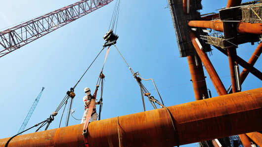 A worker stands on pipes at an offshore oil engineering company in Qingdao, in China's eastern Shandong province.