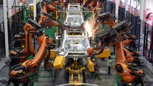 Robotic arms weld body shells of automobiles.
