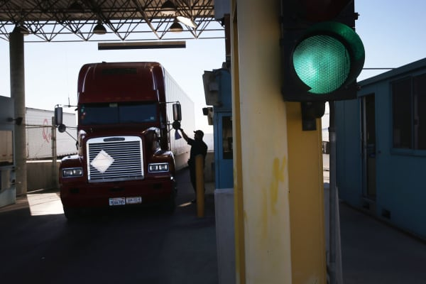 A U.S. Customs and Border Protection agent asks for documents from a truck driver coming from Mexico into the United States at the Otay Mesa port of entry in San Diego, California.
