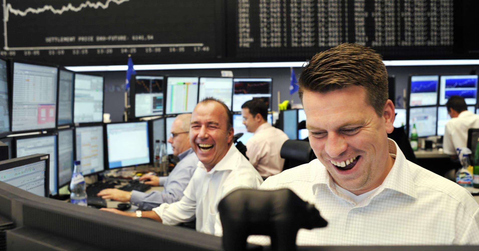 Stock brokers laugh at Frankfurt's stock exchange.
