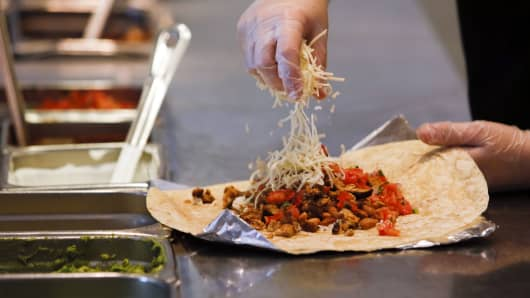 A employee sprinkles cheese on a burrito at a Chipotle Mexican Grill restaurant in Hollywood, California.
