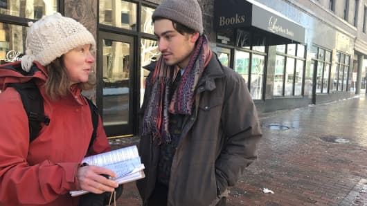 Jeremy Mack, Portland, working for Maine Peoples Alliance, gathers signatures for a referendum next year on MaineCare (Medicaid) expansion in Monument Square, Portland. Kristin Bingham, left, signs the petition.