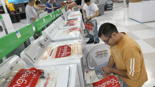 Workers prepare merchandise on the sales floor at an hhgregg store in Niles, Illinois.