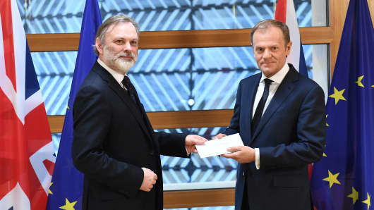 Britain's Ambassador to the EU Tim Barrow (L) shakes hands with European Council President Donald Tusk after handing him the British prime minister's formal notice of the UK's intention to leave the EU under Article 50 of the Lisbon Treaty in Brussels on March 29, 2017.
