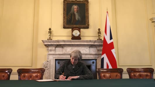 Britain's Prime Minister Theresa May, sits below a painting of Britain's first Prime Minister Robert Walpole, as she signs the official letter to European Council President Donald Tusk.