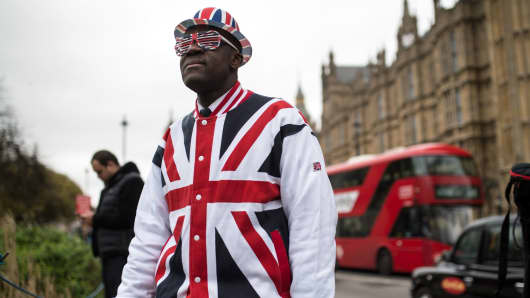A man wearing clothing featuring the Union flag stands in front of the Houses of Parliament in London, on March 29, 2017.