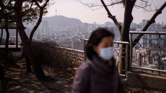 A woman wearing a face mask walks in an area overlooking the city skyline in Seoul, South Korea.