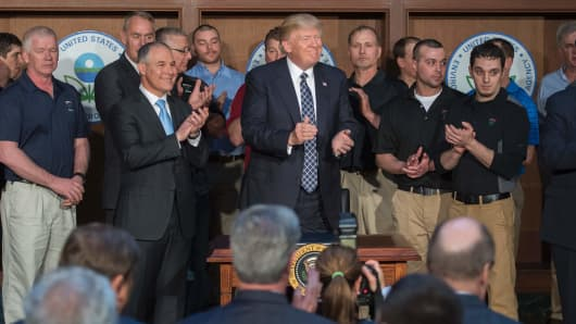 Surrounded by miners from Rosebud Mining, US President Donald Trump (C) applauds after signing the Energy Independence Executive Order at the Environmental Protection Agency (EPA) Headquarters in Washington, DC, March 28, 2017.