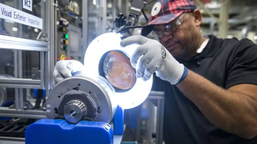 An employee inspects a component for hybrid electric vehicle motors at the Toshiba International manufacturing facility in Houston, Texas.