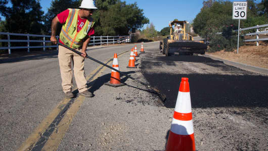 A worker repaves a road on Encino Drive in Oak View, California.