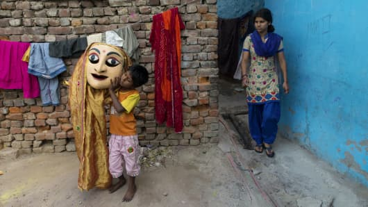 A child holds a big puppet outside his house in the Kathputhli Colony (Puppeteers' Colony) in New Delhi