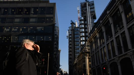 City workers shield their eyes from the low afternoon sun, near to the Lloyds building