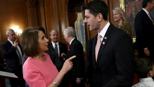 Speaker of the House Paul Ryan (R) (R-WI) speaks with House Minority Leader Rep. Nancy Pelosi (D-CA) following an event marking the passage of the 21st Century Cures Act at the U.S. Capitol December 8, 2016 in Washington, DC.