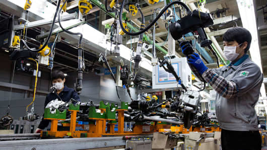 Employees assemble vehicle chassis modules on the production line at the Hyundai Mobis factory in Asan, South Chungcheong, South Korea, on Tuesday, Jan. 24, 2017