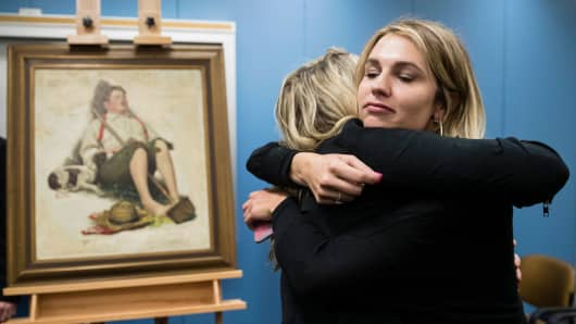 Emily Murta, right, and Kaitlin Grant embrace during a news conference regarding the newly recovered Norman Rockwell painting, that belonged to their grandfather Robert Grant and was stolen more than 40 years ago, at the federal building in Philadelphia, Friday, March 31, 2017.