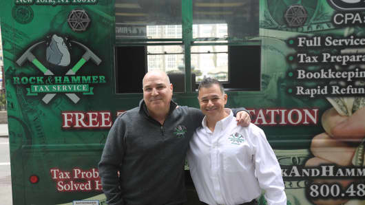 Rock & Hammer Tax Service co-founders Roger Gillman and Henry Obadiah pose in front of the tax truck.