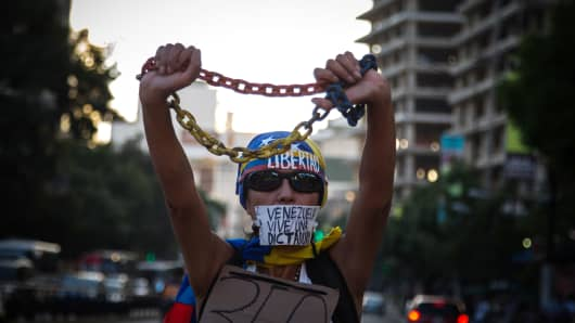 A demonstrator holds a chain and wears a sign over her mouth during a protest against the Supreme Court's decision to seize the powers of the opposition-led Congress and while the banner reads 'Venezuela lives in a dictatorship' in Caracas, Venezuela, on Friday, March 31, 2017.