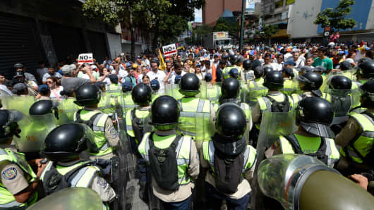 Venezuelan opposition activists take part in a protest - blocked by the National Guard - against the government of President Nicolas Maduro at the Francisco Fajardo highway in Caracas on April 1, 2017.