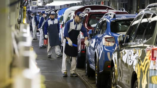Workers inspect Subaru branded vehicles on the production line of Fuji Heavy Industries' Gunma Yajima Plant in Ota, Gunma, Japan, on Thursday, March 30, 2017.