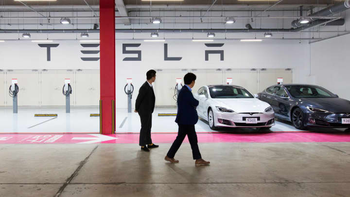 Customers look at a Tesla Model S 90D electric vehicles at a company's charging station in South Korea.
