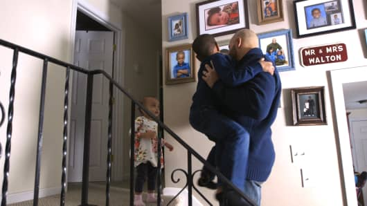Greg Walton plays with his two children in their family home in Brockton, Massachusetts