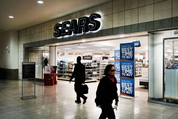 People walk by a Sears store in a nearly-empty Westfield Meriden shopping mall in Meriden, Connecticut.
