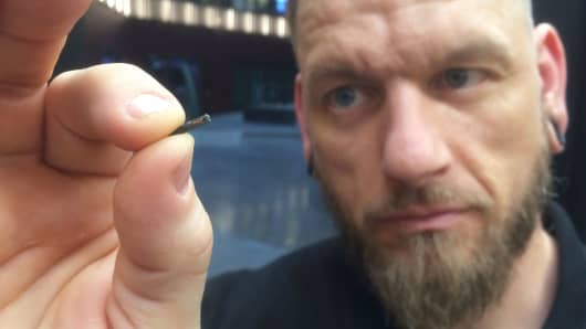 Jowan Osterlund from Biohax Sweden, holds a small microchip implant, similar to those implanted into workers at the Epicenter digital innovation business centre during a party at the co-working space in central Stockholm, Tuesday March 14, 2017.