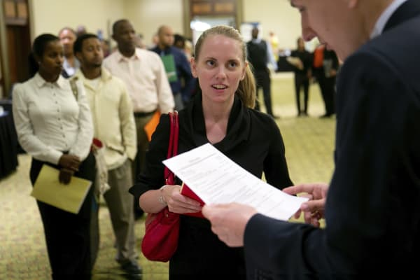 A job seeker has her resume looked at during the Choice Career Fairs job fair in Arlington, Virginia.